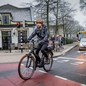 Giel Claessens op zijn snelle e-bike op de weg, achter hem de fietsers op het fietspad.